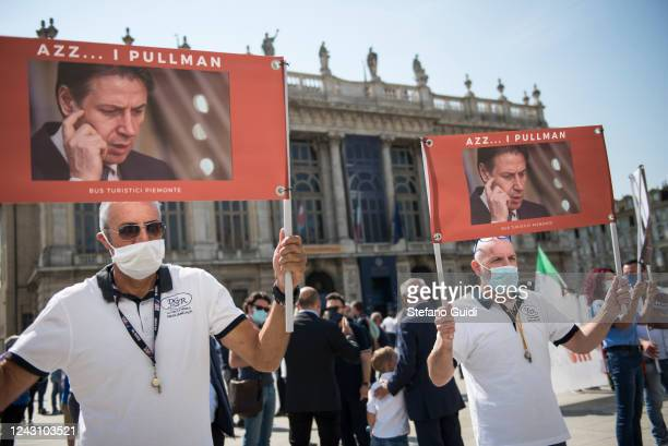 Men wearing protective face masks hold up signs during a demonstration by bus drivers against the Italian Government for the economic problems the...