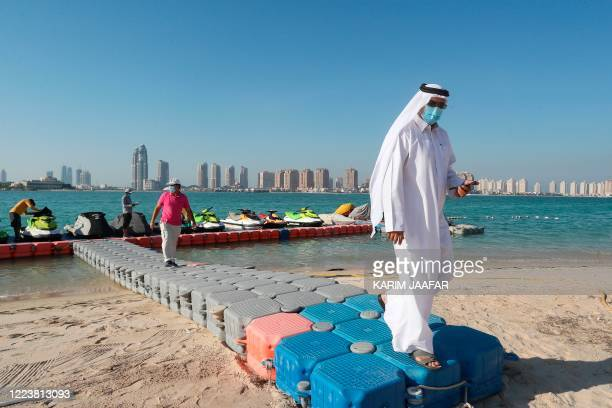 Men, wearing protective masks, walk on a plastic pier at Katara beach in the Qatari capital Doha on July 1, 2020 as the country moves into the second...