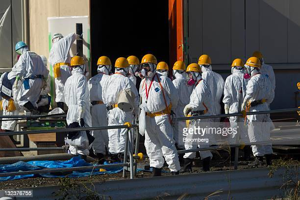 Men wearing protective suits and masks work at the crippled Tokyo Electric Power Co Fukushima DaiIchi nuclear power station in Okuma Town Fukushima...