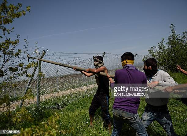 Men wearing scarves over their mouths use a pole to try and bring down the border fence between Greece and Macedonia near the Greek village of...