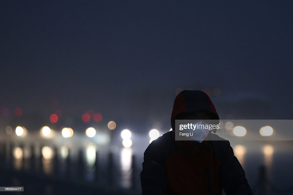 A men wearing the mask rides a bicycle on the street during severe pollution on January 29, 2013 in Beijing, China. The 4th dense fog envelops Beijing with pollution at hazardous levels in January.