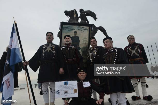 Men wearing traditional clothing pose next to the statue of Alexander the Great as people start to gather prior to a protest against the use of the...
