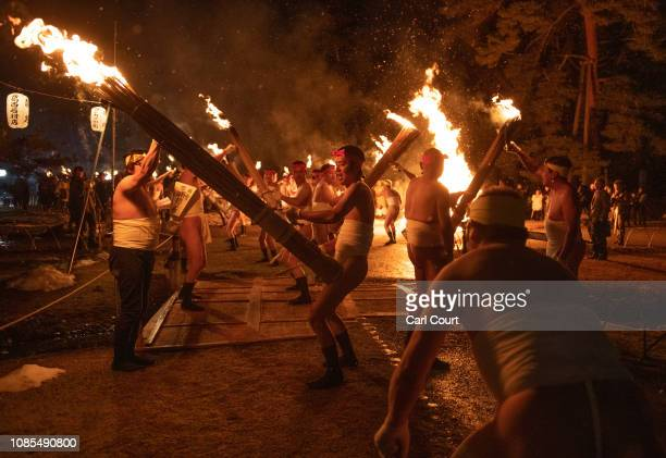 Men wearing traditional 'shimekomi' loincloths and carrying torches sing and dance in Motsuji Temple during the Hatsukayasai festival on January 20...