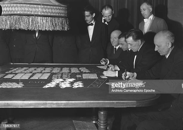 Men wearing tuxedos portrayed while playing at the roulette table San Remo Casino 1950