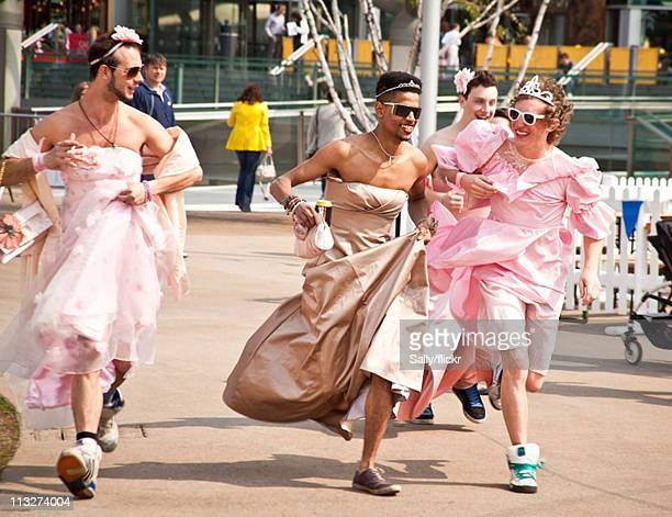 Men wearing wedding dresses rush to watch the Royal Wedding of Prince William to Catherine Middleton on April 29 2011 in Liverpool England The...