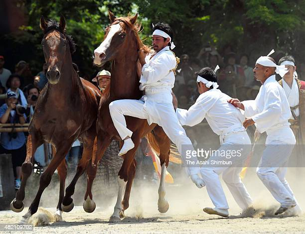 Men wearing white clothes called 'Okobito' try to capture a bareback horse with bare hands during the 'Nomakake ' ritual to dedicate horses to the...