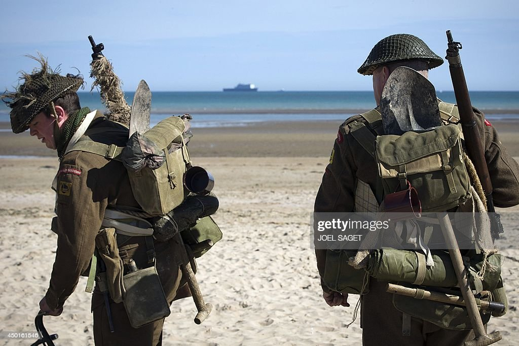 Men wearing WWII British uniforms walk on June 6, 2014 in