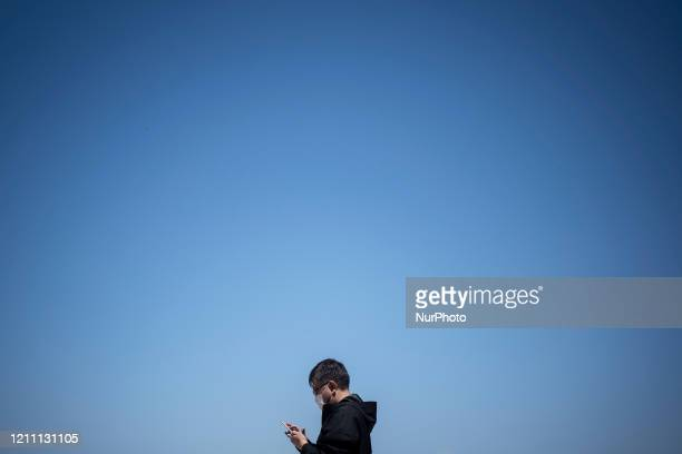 A men wears mask walk during the Coronavirus lockdown crisis April 25 2020 Prime Minister Shinzo Abe's state of emergency has led to temporary...