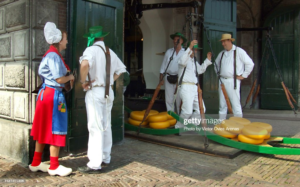 Men weighing cheese and woman in traditional Dutch custome at the Cheese Market in Alkmaar's main square in the Netherlands : Stock Photo