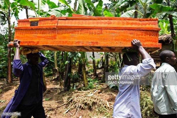 Men who lost relatives after the Sume river burst its banks carry a coffin in the eastern village of Wanjenwa in Uganda's Bududa district on October...