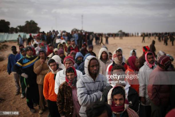 Men who recently crossed into Tunisia from Libya wait in line for food in a United Nations displacement camp on March 10 2011 in Ras Jdir Tunisia As...