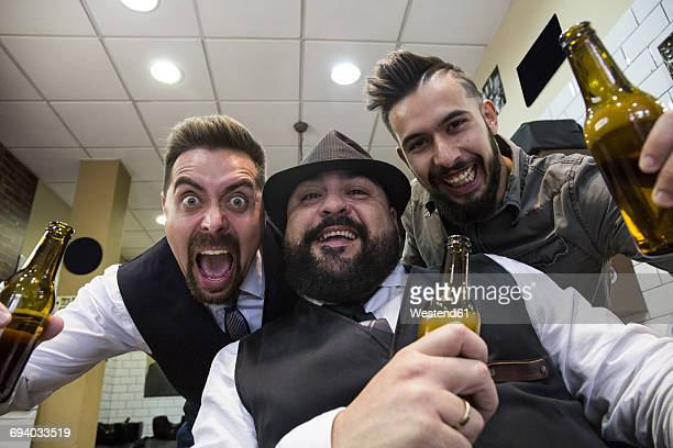 Men with beers laughing in front of the camera in a barbershop