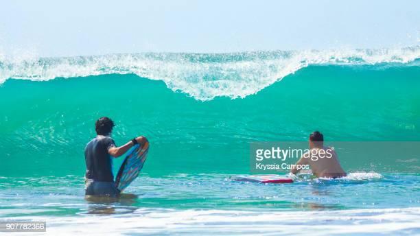 men with bodyboard in front of a crashing wave - parque nacional de santa rosa fotografías e imágenes de stock