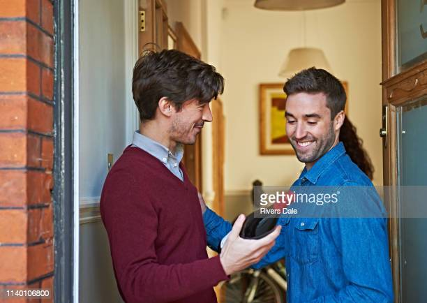 men with bottle of wine smiling at front door - maroon stock pictures, royalty-free photos & images