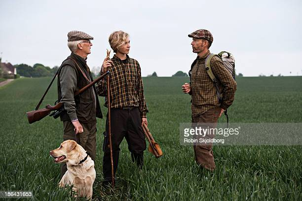 Men with dog and rifle standing in field
