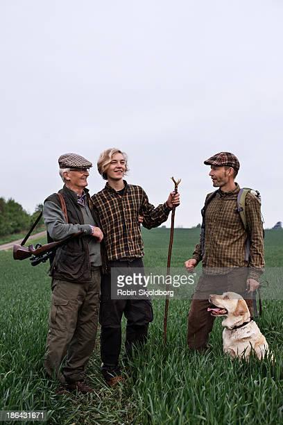 Men with dog talking in field