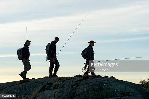 Men with fishing rods walking on coast