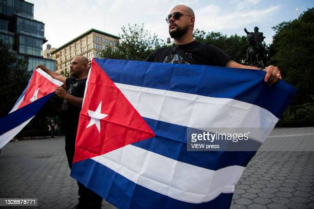 Men with flags gather to accompany Cuban protesters in Union Square Park on July 14, 2021 in New York City. A small group of people gathered in Union...