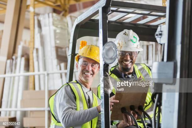 Hommes avec chariot élévateur en regardant presse-papiers