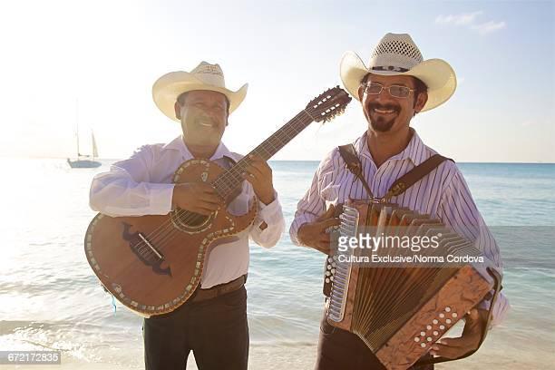 men with guitar and accordion by sea smiling, isla mujeres, mexico - mujeres fotos stockfoto's en -beelden