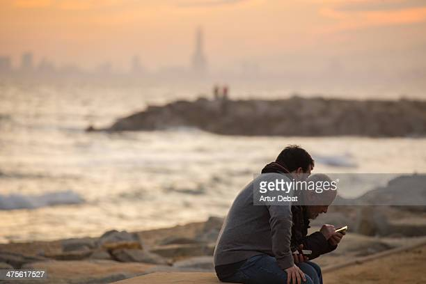 Men with his smartphone sharing moments in the beach at sunset