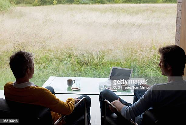Men with laptop and coffee sitting at window with view of rural field