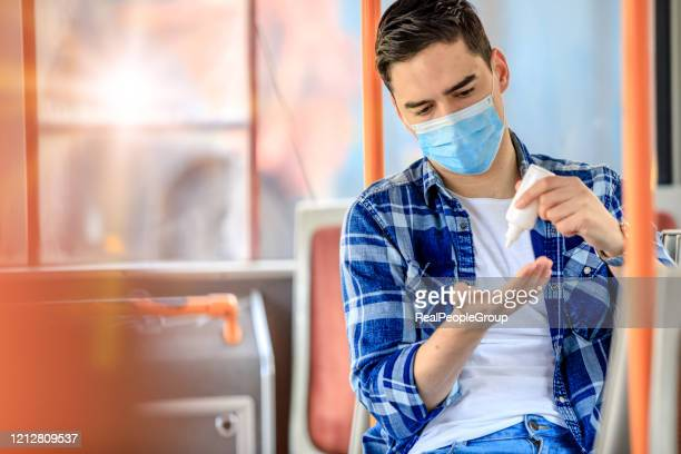 men with mask using hand sanitizer preventing contagion - antiseptic stock pictures, royalty-free photos & images