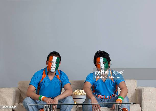 Men with painted face sitting on sofa with bowl of popcorn on table at home