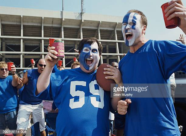 men with painted faces holding red cup in stadium parking lot - face paint stock pictures, royalty-free photos & images