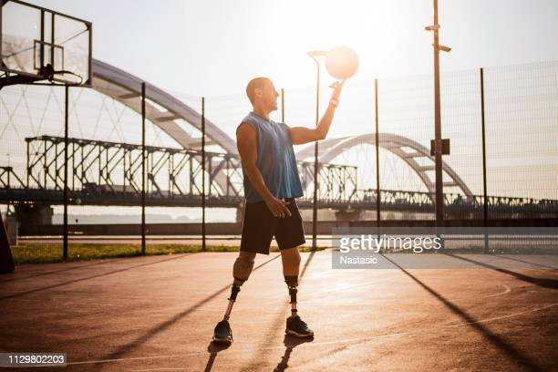 men with prosthetic legs on basketball court against morning sun spinning boll on a finger - spinal cord injury stock photos and pictures