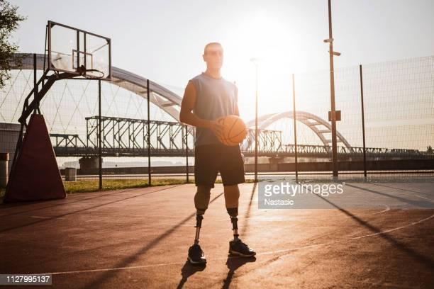 homens com pernas protéticas na quadra de basquete contra o sol da manhã - só um homem - fotografias e filmes do acervo