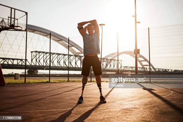 men with prosthetic legs on basketball court against morning sun stretching - artificial limb stock pictures, royalty-free photos & images