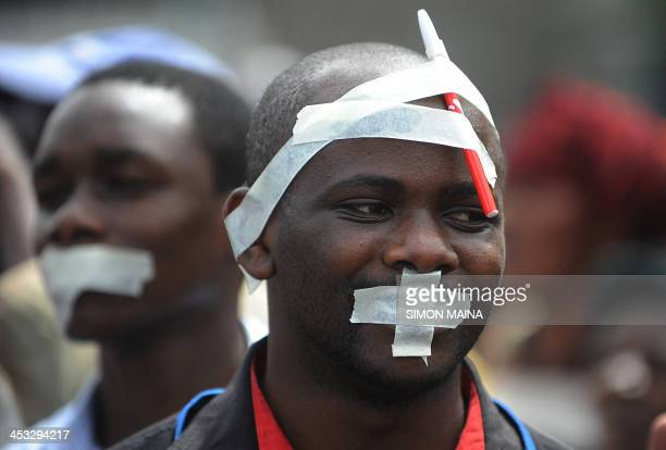 Men with tape on their faces take part in a march called by Kenyan journalists on december 3 2013 in Nairobi to protest a bill voted par the...
