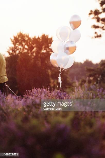 men with white balloons in field - releasing stock pictures, royalty-free photos & images