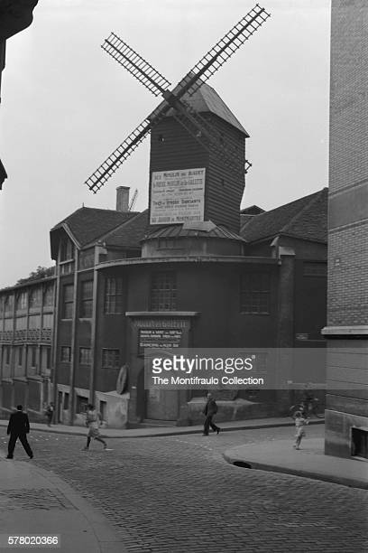 Men women and a child during the second World Wars occupation of France walking past the Moulin de la Galette and Radet windmill situated near the...