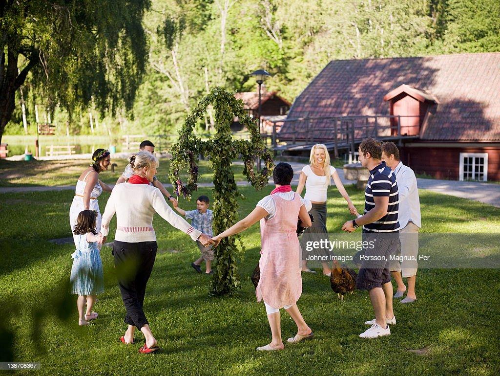 Men, women and children dancing in circles : Stock Photo