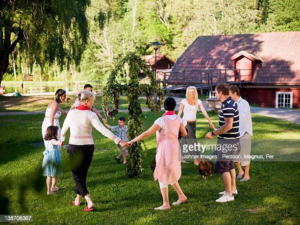 Men, women and children dancing in circles