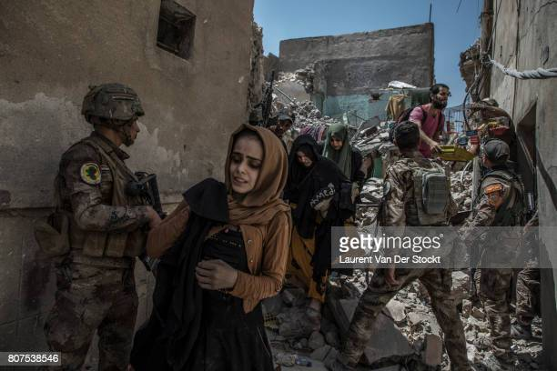 Men women and children emerge from the rubble of alNuri mosque complex on June 29 in Mosul Iraq The Iraqi Army Special Operations Forces and...