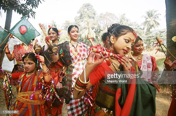 Men women and children sing and dance at a rally that starts from the Institute of Fine Arts to celebrate the occasion of Nobanno Utshob or Harvest...