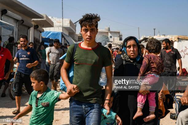 Men, women, and children walk past make-shift brick shelters at a camp for the displaced during a demonstration by Syrians along the border with...