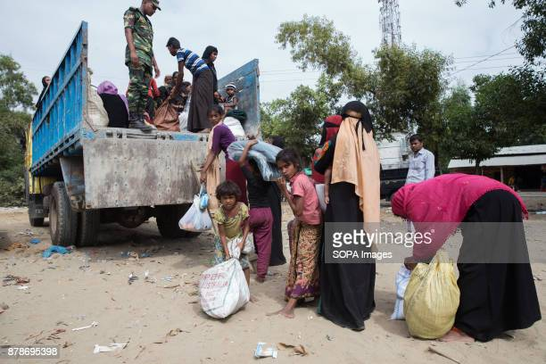 Men women children and babies are loaded into trucks to be taken to a nearby refugee camp soon after they arrive in Bangladesh Thousands of Rohingya...