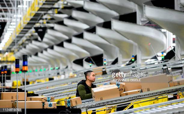 Men work at a distribution station in the 855000squarefoot Amazon fulfillment center in Staten Island one of the five boroughs of New York City on...