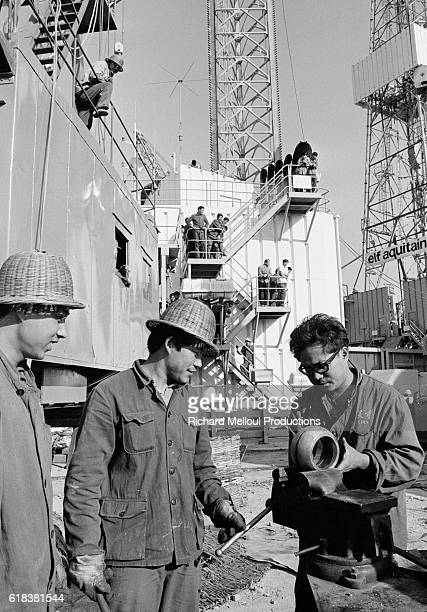 Men work at an oil rig in China owned by the French company Elf Aquitaine