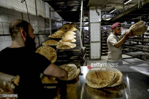 Men work at bakery that makes traditional flatbread in the Lebanese capital Beirut, on February 26, 2021. - Lebanon is locked in its worst economic...