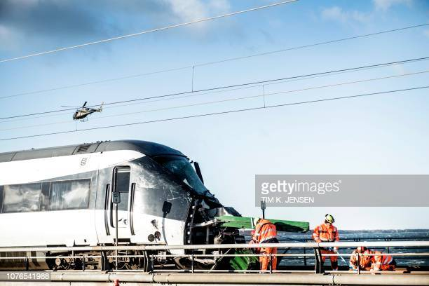 TOPSHOT Men work at the accident site next to a passenger train standing on the rails in Nyberg Denmark after the Great Belt Bridge was closed...