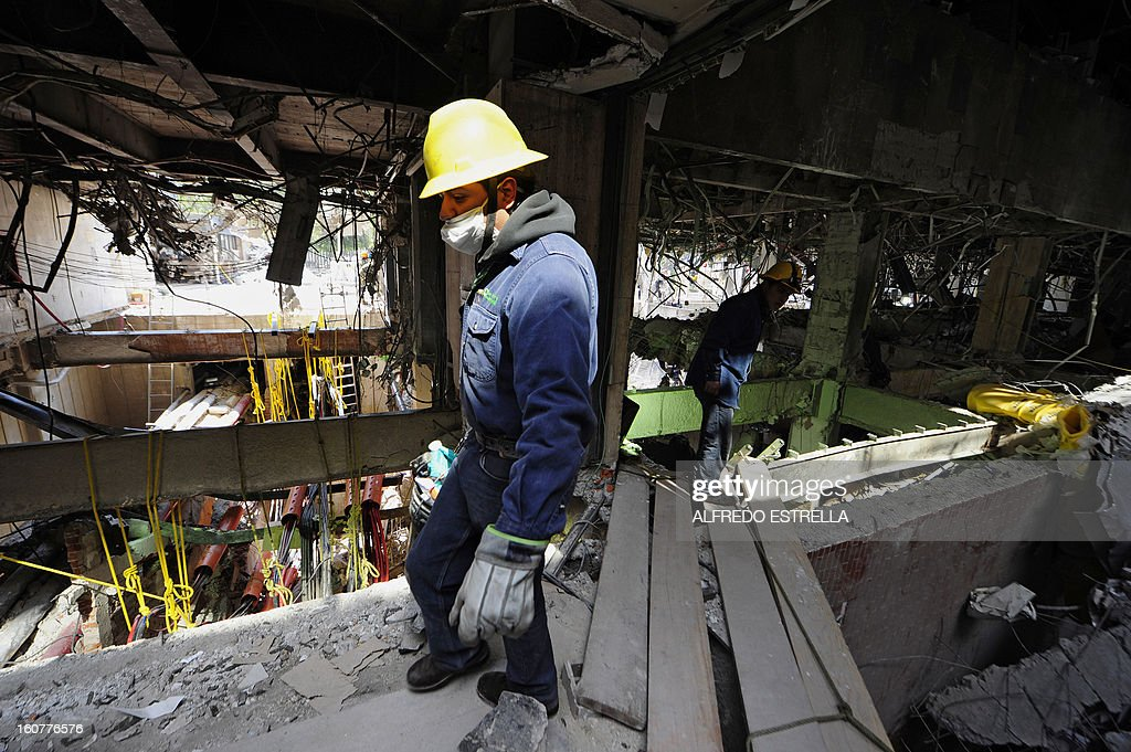 Men work in the damaged building of Mexican state-owned oil giant Pemex, after a blast, in Mexico City on February 5, 2013. A gas build-up caused the explosion that rocked the headquarters of Mexico's state-owned oil firm last week, killing 37 people, officials said Monday, ruling out a bomb attack. The explosion also injured morfe than 120 people. AFP PHOTO/Alredo Estrella