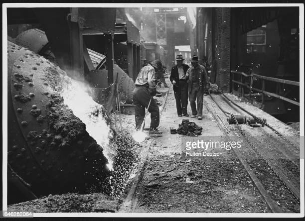 Men work near a converter which begins to pour