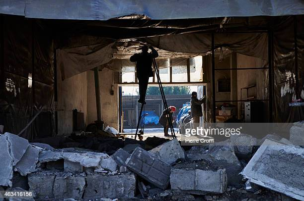 Men work on a damaged building as fighting continues in the area on February 14 2015 in Donetsk Ukraine Missiles fired from the direction of...