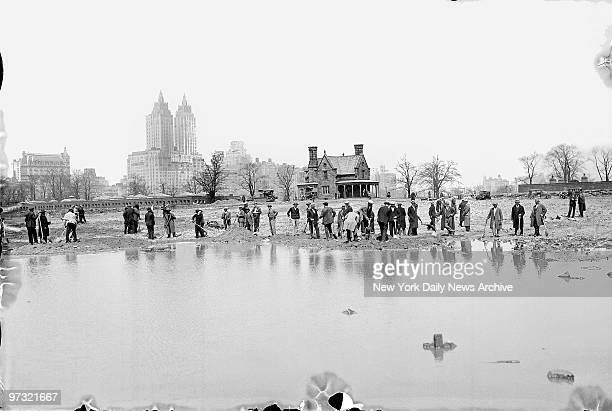 Men work on finally filling in the site of the old Central Park Lower Reservoir when the city found money to truck in dirt and pay workers to remove...