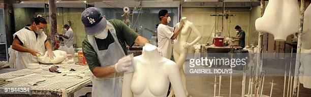 Men work on mannequins at Patina V in City of Industry California on September 29 2009 Patina V is a company providing mannequins for store windows...